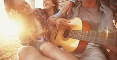 Teenagers listening to guy playing his guitar - stock footage