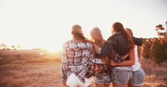 Teen girls facing the sunset with on a summer evening Stock Footage
