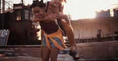 Afro girl piggybacking her teen girl friend Stock Footage
