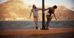 Afro girl and grungy friend hanging out at the harbor - stock footage