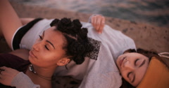 Teen grunge girl friends lying together alongside water Stock Footage