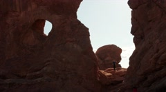 Man taking picture under arch in arches national park Stock Footage