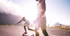 Mixed racial group of teen longboarders on road Stock Footage
