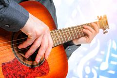 hand to pluck the strings of a guitar - stock photo