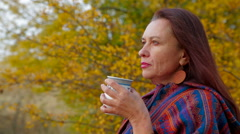 Woman Of Middle Age Drawing A Picture At Plein Air with mug of cocoa in winter Stock Footage