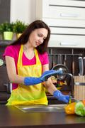 Young woman cleaning kitchen Stock Photos