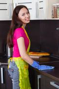 Beautiful brunette cleans the kitchen furniture - stock photo