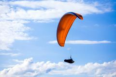 Paraglider flying on blue sky Stock Photos