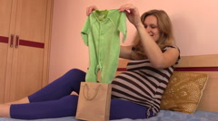 Pregnant woman unpack baby crawlers rompers from shop bag Stock Footage