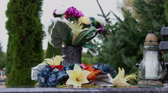 Close up of wreath, candle and flowers on the tombstone Stock Footage