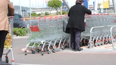 Woman on parking place with shopping cart.  0116 Stock Footage