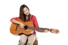 Pretty teenage girl singing a song while playing an acoustic gui Stock Photos