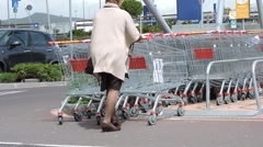 Woman with shopping cart at mall parking. - stock footage
