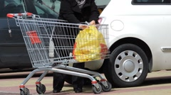 Senior woman unloading shopping cart at mall parking place Stock Footage