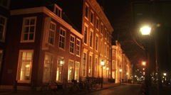 THE HAGUE Streetview Lange Voorhout by night facades, lanterns+ cyclist Stock Footage