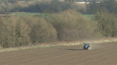 Tractor-mounted fertiliser distributor in use. - stock footage