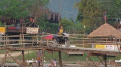 A motorcycle over wooden bridge,Vang Vieng,Laos Stock Footage