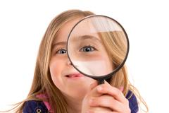 Blond indented girl with eye in magnifying glass - stock photo