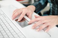 Female hands working on a laptop computer keyboard Stock Photos