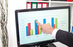 Businessman showing a graph on the screen - stock photo