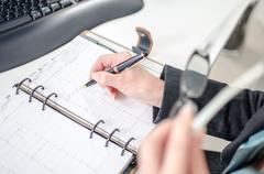 Businesswoman noting an appointment in her diary - stock photo