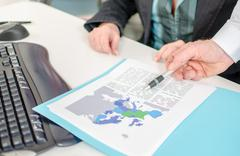Businessman showing an economic document with a pen Stock Photos