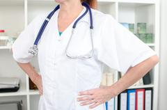 Female doctor holding her hands on her hips - stock photo
