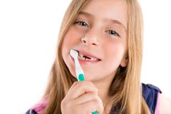 Blond kid indented girl cleaning teeth toothbrush - stock photo