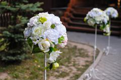 Beautiful white flower arrangements decorated the track for the wedding cerem Stock Photos