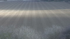 Shadows of clouds move across a newly tilled field. Stock Footage