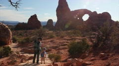 A mother and kids hiking at turret arch in arches national park Stock Footage