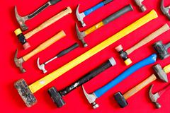 Multiple hammers on a vivid red background Stock Photos