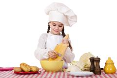 Beautiful little chief cooker on the desk with vegetables - stock photo