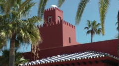 Bil Bil castle red building moving palms deep blue sky Andalucia Stock Footage