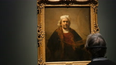 Man looking at Rembrandt self-portrait Stock Footage