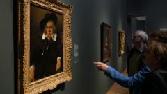 Visitors looking at Rembrandt painting, gesturing Stock Footage