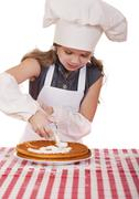 Beautiful happy seven year old girl in chef uniform with shortcakes and whipp - stock photo