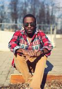 Fashion portrait of stylish young african man listens to music outdoors, wear - stock photo