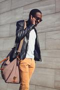 Outdoor portrait of young african man walking and talking on the smartphone i Stock Photos