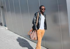 Street fashion concept - handsome stylish young african man walks evening in  - stock photo