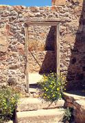Stone wall with a door of the ancient city - stock photo