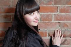 Young woman with long brown hair  looks back copy space on red brick wall - stock photo