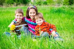 Three smiling kids on green meadow - stock photo