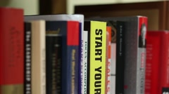 Tilting down then up on the spines of business books Stock Footage