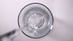 Pouring Water into Glass from Above Slow Motion Stock Footage