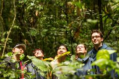 Group Of Tourists In Ecuadorian Jungle Looking For Animals In Cuyabeno Wildlife - stock photo
