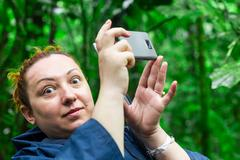 Funny Face Of Tourist Woman Into The Jungle While Snapping A Photo With Her Stock Photos