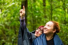 Group Of Two Adult Tourist Woman Into The Jungle Pointing To Left Upper Corner - stock photo