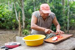 Stock Photo of Rural Chef Preparing Lunch Outdoor Seating Against Dense Vegetation