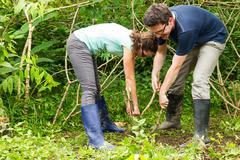 Couple Of European Tourists Extracting Yucca Or Cassava Plant From The Ground Stock Photos